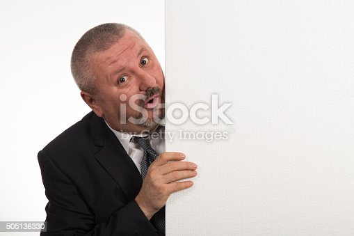 istock Mature businessman holding a white panel and gesturing 505136330