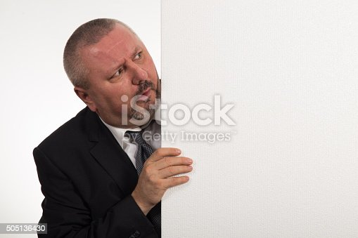 istock Mature businessman holding a white panel and gesturing 505136430