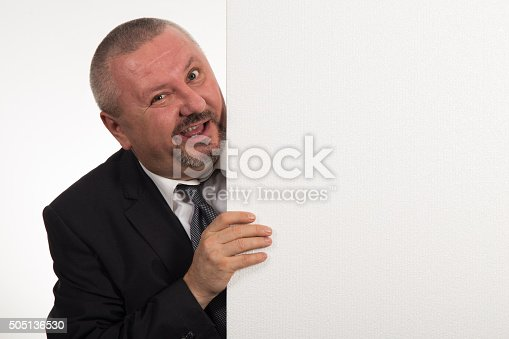 istock Mature businessman holding a white panel and gesturing 505136530