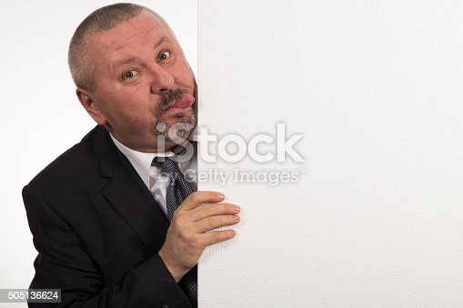 istock Mature businessman holding a white panel and gesturing 505136624