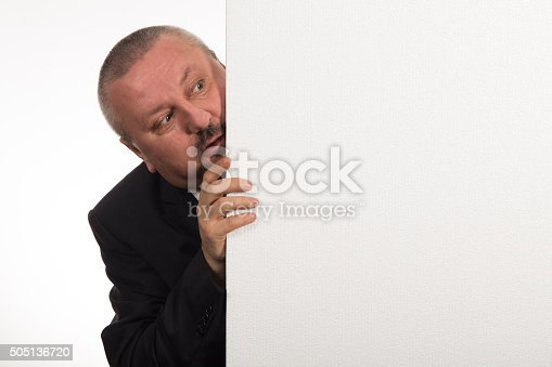 istock Mature businessman holding a white panel and gesturing 505136720