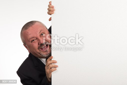 istock Mature businessman holding a white panel and gesturing 505136836