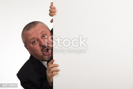 istock Mature businessman holding a white panel and gesturing 505136940