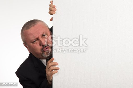 istock Mature businessman holding a white panel and gesturing 505137032