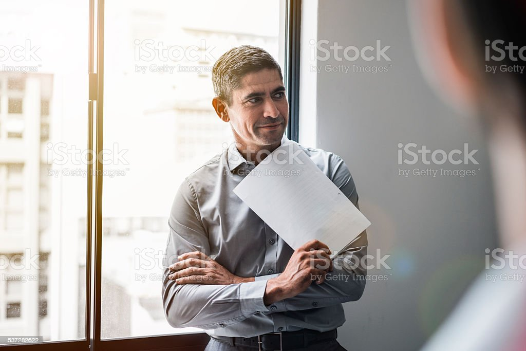 Mature businessman holding document in meeting stock photo