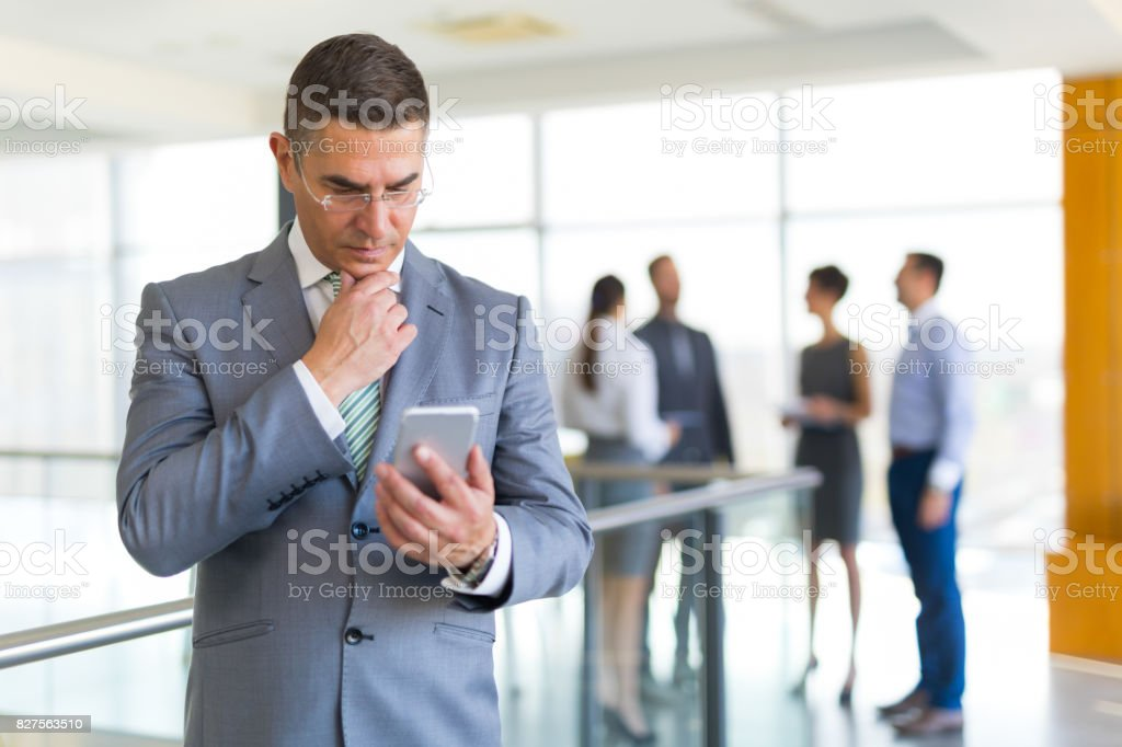 Mature  businessman holding mobile phone and reading text message. stock photo