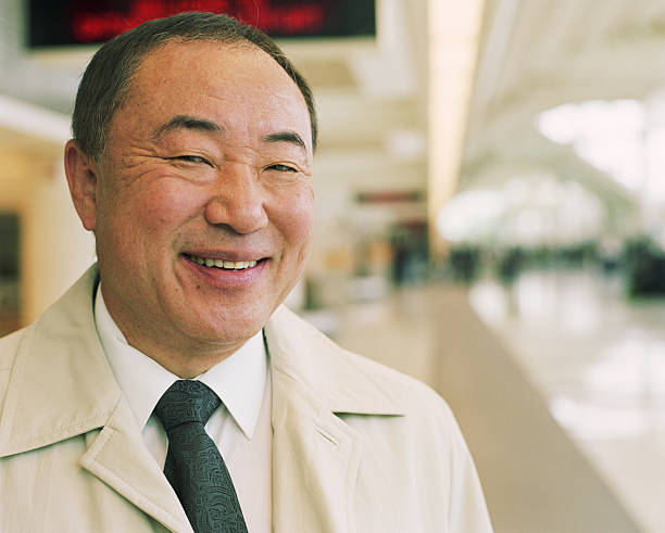 Mature businessman in airport, smiling stock photo