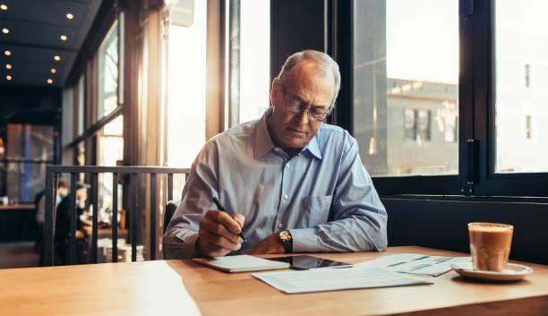Reife Geschäftsmann im Café Notizen – Foto