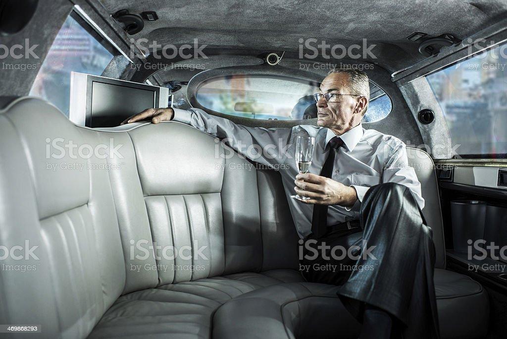 Mature businessman in limousine. stock photo