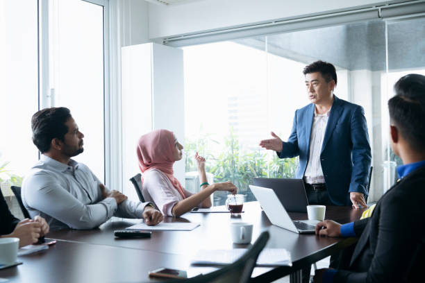Mature businessman in meeting with colleagues Multi racial group of business people sitting around meeting table and listening to male manager business Malaysia stock pictures, royalty-free photos & images