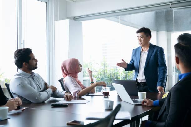 homme d'affaires mature en réunion avec des collègues - business malaysia photos et images de collection