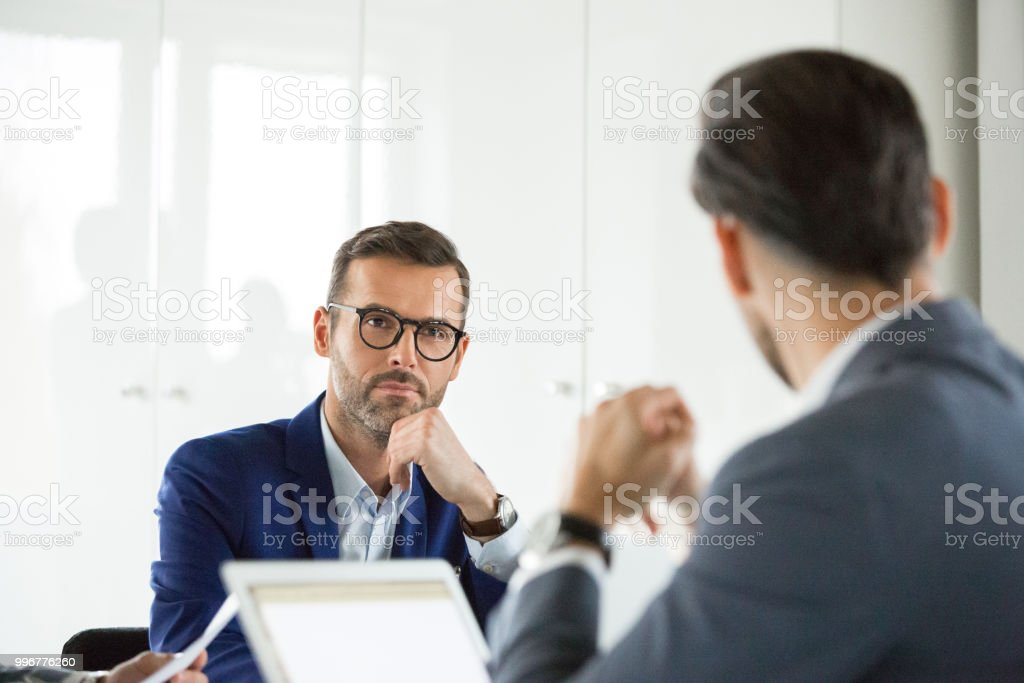 Mature businessman in meeting with colleagues Mature businessman in meeting with colleagues. Corporate professional listening to conversation during meeting in office. Adult Stock Photo