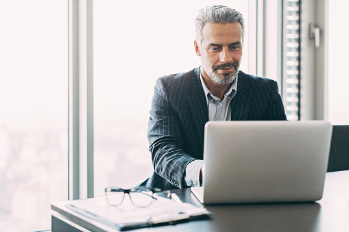 Mature businessman typing on a laptop in his office, with copy space.