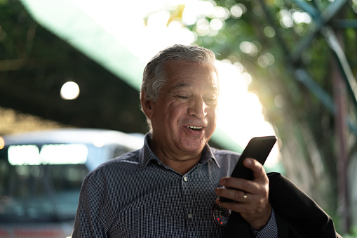 Mature Businessman Laughing holding mobile