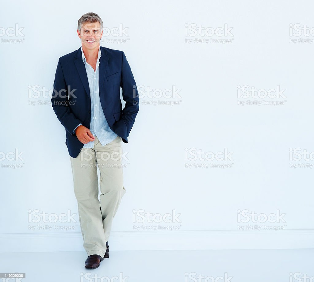 Mature businessman leaning against white background stock photo