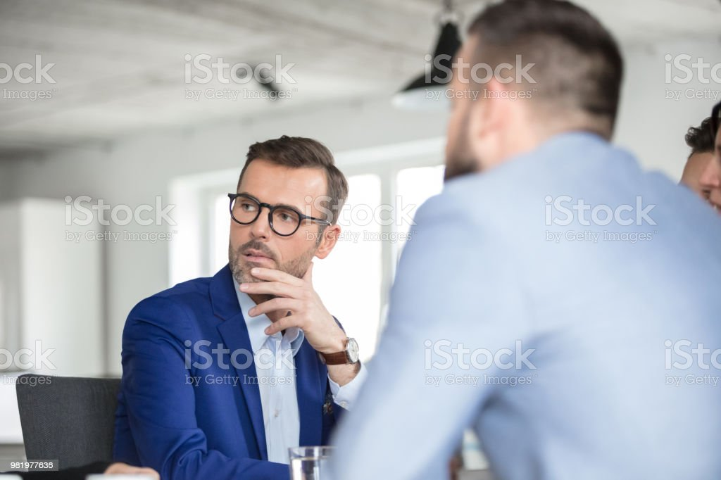 Mature businessman listening to discussion in meeting Mature businessman listening to discussion in meeting. Conference meeting of corporate professionals. Adult Stock Photo