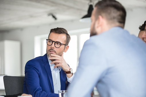 Mature Businessman Listening To Discussion In Meeting Stock Photo - Download Image Now