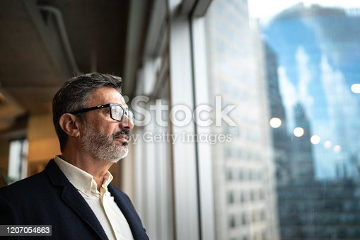 Mature businessman looking out of window