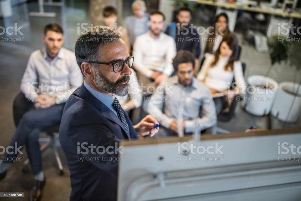 Mature businessman making a plan for his colleagues on a training class. stock photo