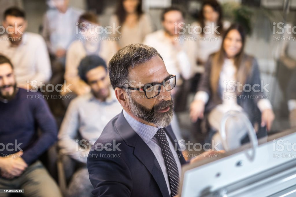 Mature businessman making a plan for his colleagues on a training class. royalty-free stock photo