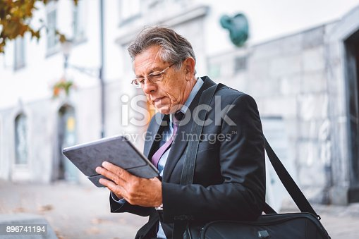 istock Mature businessman multitasking while taking a lunch break in the city 896741194