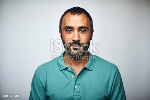 Portrait of mature businessman. Executive is wearing T-shirt. He is against white background.