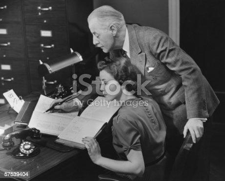istock Mature businessman overseeing secretary's work, (B&W) 57539404
