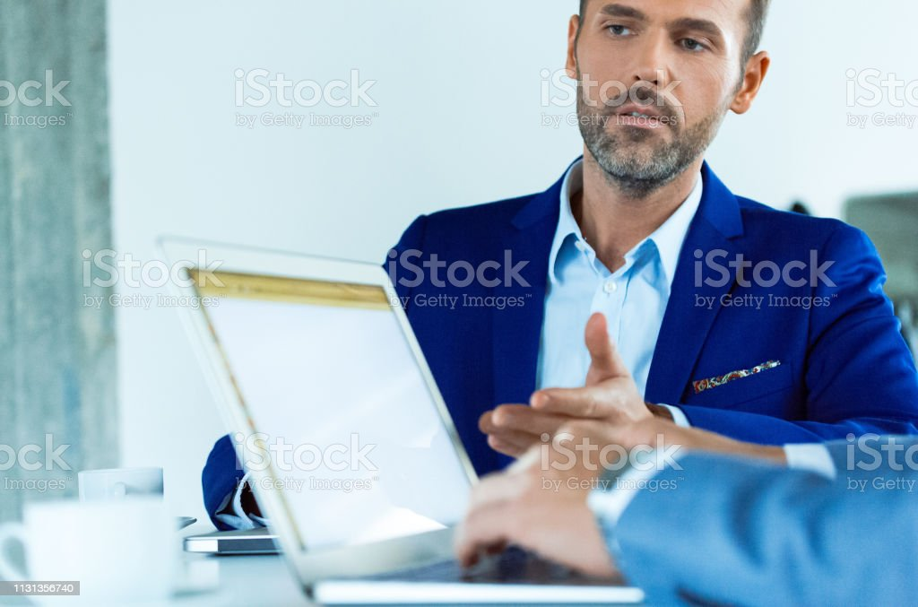 Mature businessman planning with colleague at desk Mature businessman gesturing at laptop to colleague during meeting. Male professionals are discussing at desk. They are planning at creative office. 30-39 Years Stock Photo