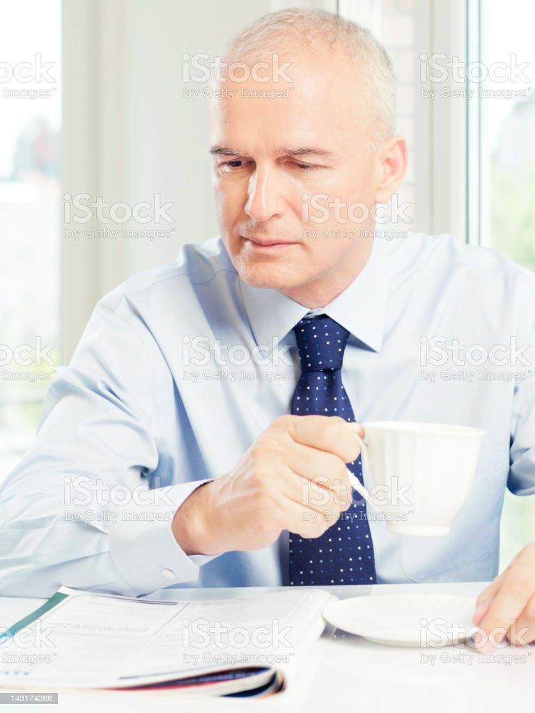 mature businessman reading magazine royalty-free stock photo