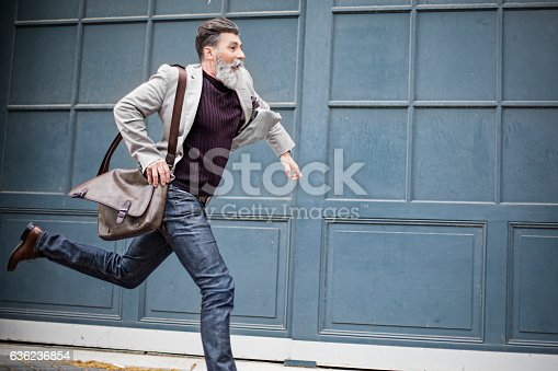 Mature businessman with a handbag running on the city street