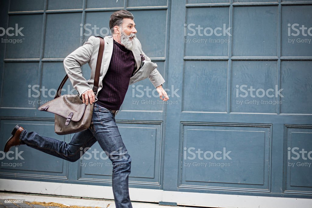 Mature businessman rushing to work stock photo