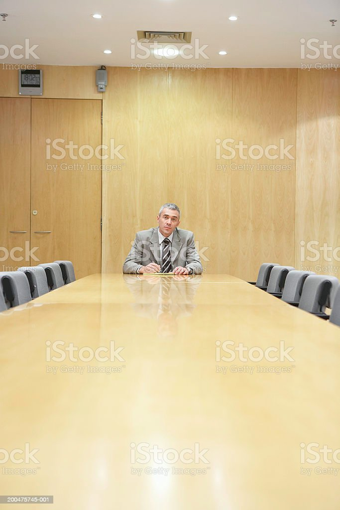 Mature businessman sitting at conference table in boardroom