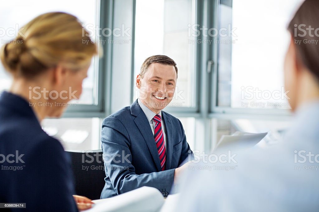 Mature businessman sitting in a meeting with colleague stock photo