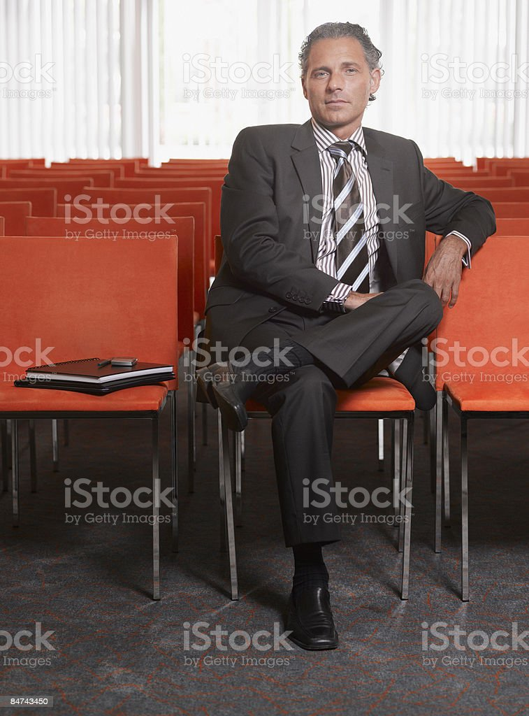 Mature businessman sitting in lecture hall royalty-free stock photo