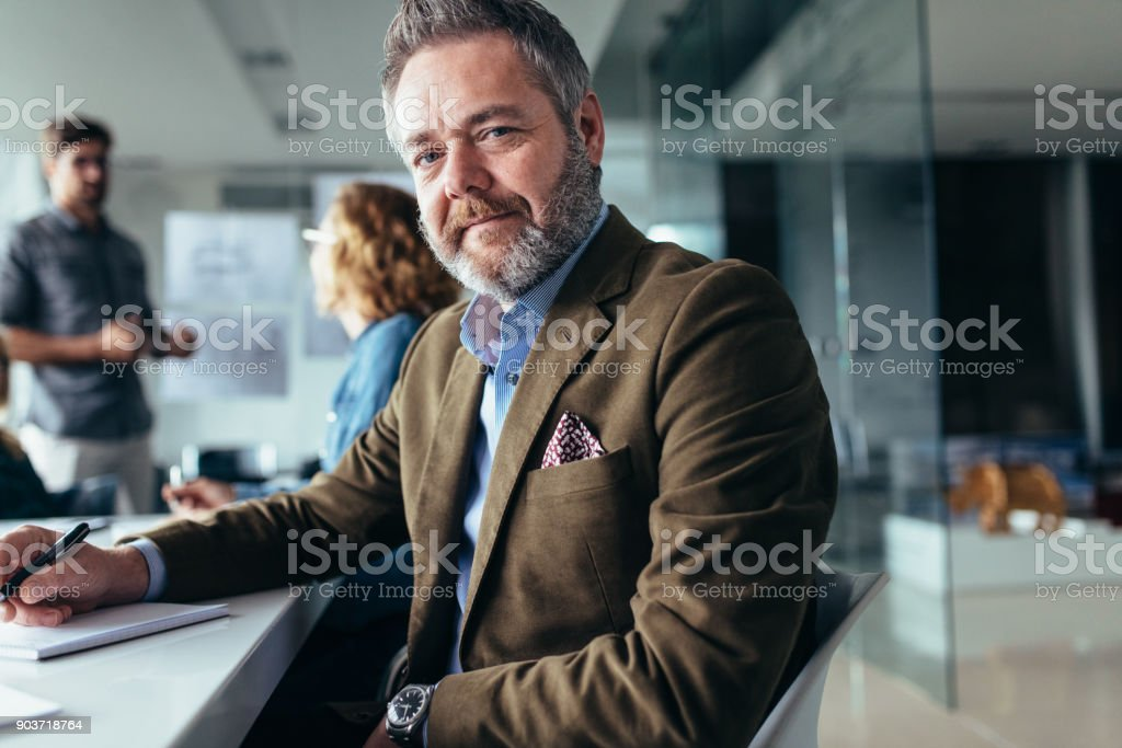 Mature businessman sitting in meeting room stock photo