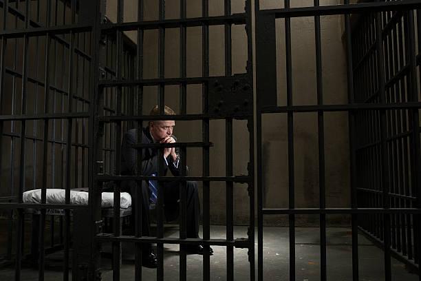 Reifer Geschäftsmann, sitzen auf dem Bett in Gefängniszelle – Foto