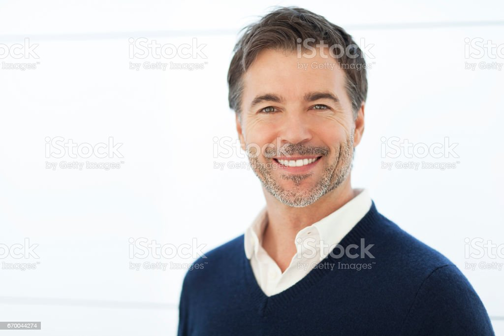 Mature Businessman Smiling At The Camera. Isolated On White. men, 50-59 years, mature men, smiling, isolated on white, healthy lifestyle, senior adult, ceo, attractive male, human face, tranquil scene, males, 40-49 years, success, portrait, male beauty, leadership, sales occupation, beard, fashion model, one person, casual clothing, adult, close-up, caucasian ethnicity, cool, confidence, indoors, copy space, brown hair, elegance, lifestyles, head and shoulders, positive emotion, glamour, human hair, satisfaction, aspirations, energy, joy, content, attitude, masculinity, green eyes, 50s 40-49 Years Stock Photo