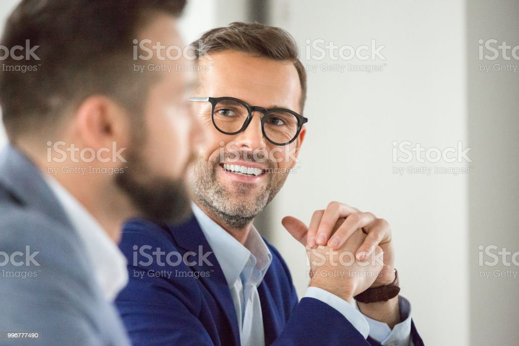 Mature businessman smiling in meeting Smiling mature businessman sitting at meeting. Business team during meeting in office. Adult Stock Photo