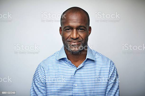 Portrait of mature businessman. Male executive is wearing shirt. Professional is smiling against white background.