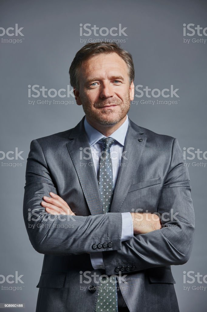 Mature businessman standing arms crossed stock photo