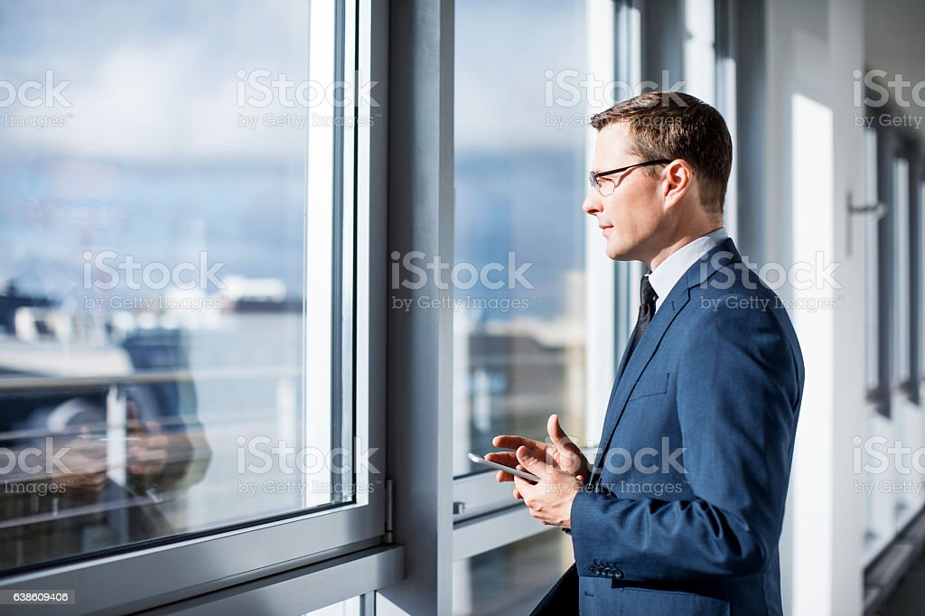 Mature businessman standing by window in office stock photo