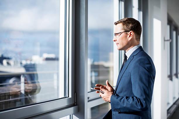 mature businessman standing by window in office - amministratore delegato foto e immagini stock
