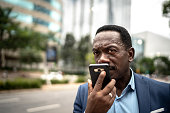 Mature businessman talking on mobile phone while walking on the street