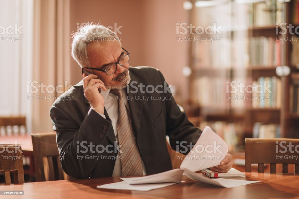 Mature businessman talking on the phone while reading reports in the office. stock photo