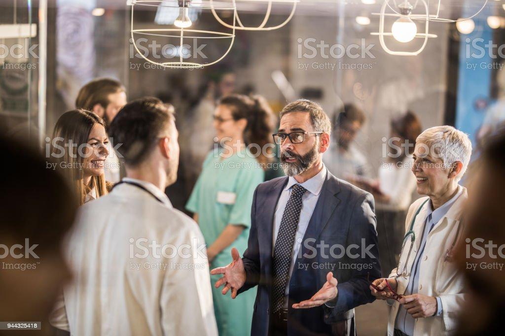 Rijpe zakenman praten met artsen in een ziekenhuis-hal. foto