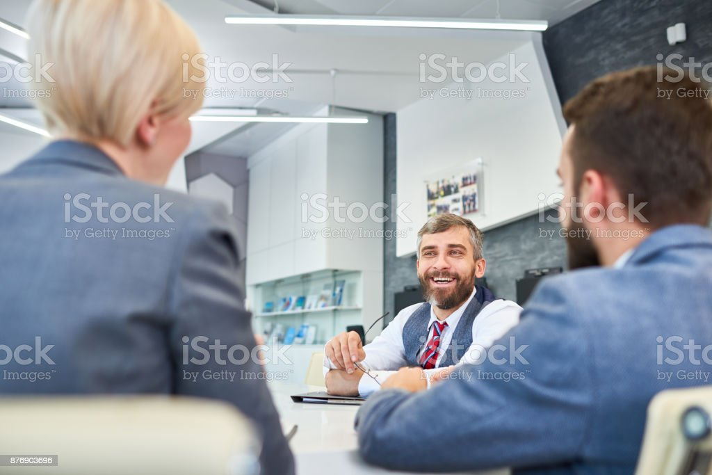 Mature Businessman Talking to Partners in Meeting stock photo