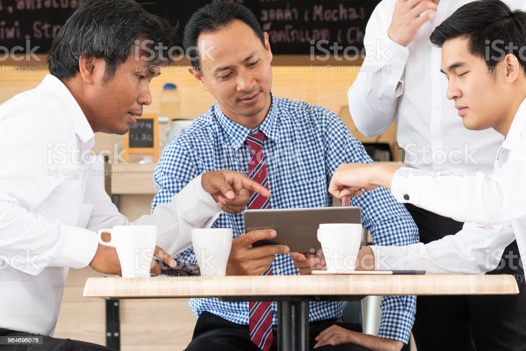 Mature businessman using a digital tablet to discuss information analyzing brainstorming with younger colleague at coffee shop royalty-free stock photo