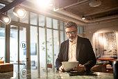 Mature businessman using digital tablet at modern office