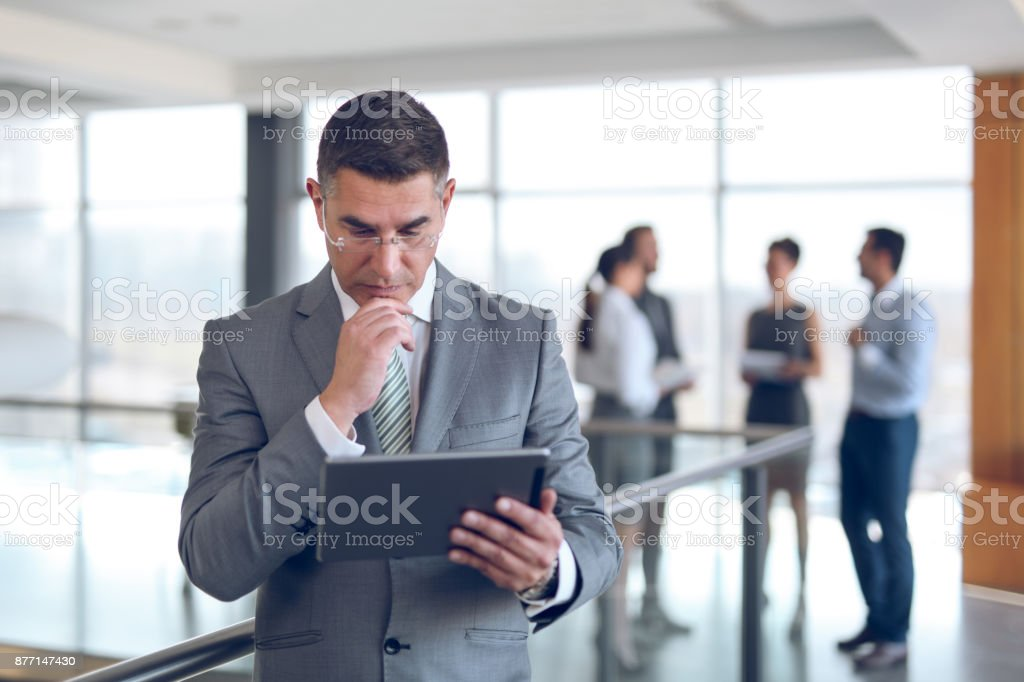 Mature businessman using digital tablet in office building hallway. stock photo