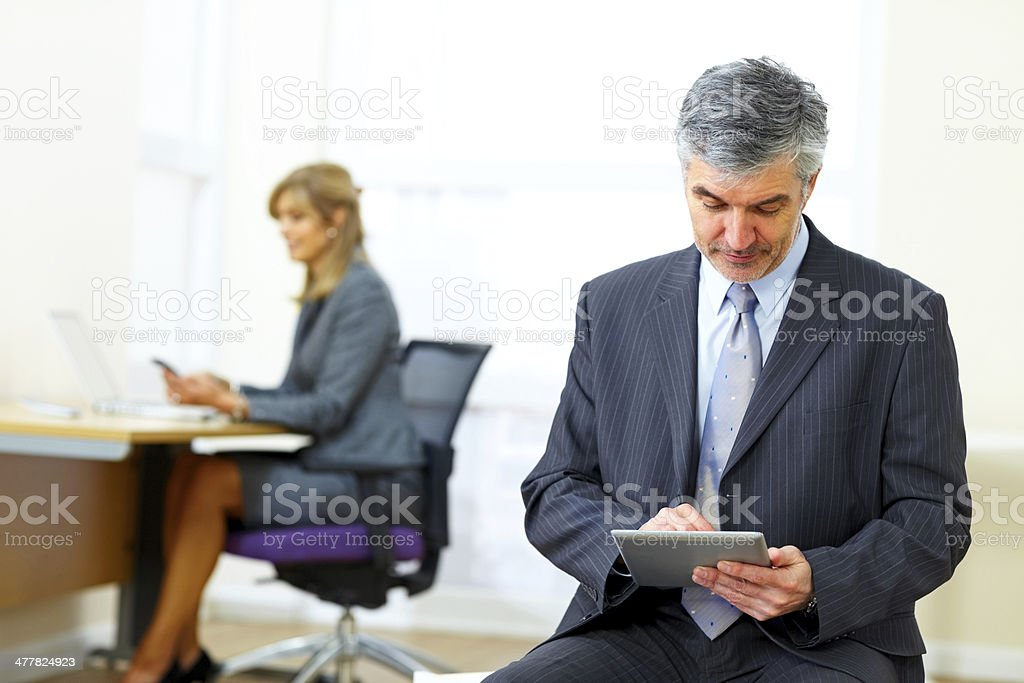Mature businessman using digital tablet in office royalty-free stock photo